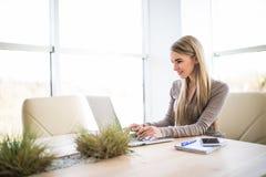 Νέα επιχειρησιακή γυναίκα χρησιμοποιώντας και δακτυλογραφώντας στο lap-top πληκτρολογίων στο γραφείο Στοκ φωτογραφίες με δικαίωμα ελεύθερης χρήσης