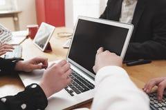 Νέα επιχειρησιακή ομάδα που εργάζεται στο γραφείο γραφείων με ηλεκτρονικό devic Στοκ Εικόνες