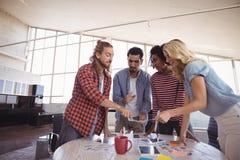 Νέα επιχειρησιακή ομάδα που συζητά μαζί από το δημιουργικό γραφείο Στοκ εικόνες με δικαίωμα ελεύθερης χρήσης