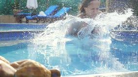Νέα λεπτή γυναίκα στο ρόδινο μπικίνι που πηδά στην πισίνα στο σε αργή κίνηση και ράντισμα νερού στο όμορφο bokeh φιλμ μικρού μήκους