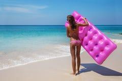 Νέα λεπτή γυναίκα sunbath με το στρώμα αέρα στην τροπική παραλία στοκ εικόνα