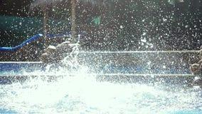 Νέα λεπτή ευτυχής γυναίκα στο ρόδινο μπικίνι που πηδά στην πισίνα στο σε αργή κίνηση και ράντισμα νερού στο όμορφο bokeh απόθεμα βίντεο