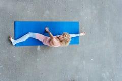 Νέα λεπτή ξανθή γυναίκα που κάνει τις ασκήσεις γιόγκας στοκ εικόνες