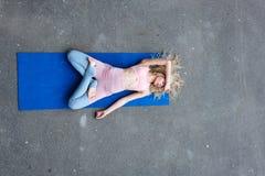 Νέα λεπτή ξανθή γυναίκα που κάνει τις ασκήσεις γιόγκας στοκ εικόνα