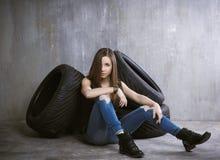 Νέα, λεπτή συνεδρίαση κοριτσιών στις ρόδες αυτοκινήτων σε ένα υπόβαθρο γκρίζου ομο Στοκ φωτογραφία με δικαίωμα ελεύθερης χρήσης
