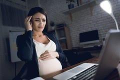Νέα εργασία εγκύων γυναικών στο σπίτι μόνο Η έγκυος γυναίκα δοκιμάζει τον πονοκέφαλο Στοκ φωτογραφίες με δικαίωμα ελεύθερης χρήσης