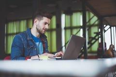 Νέα εργασία επιχειρηματιών στην αρχή, καθμένος στο γραφείο, εξετάζοντας την οθόνη φορητών προσωπικών υπολογιστών, χαμόγελο στοκ φωτογραφίες