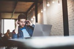 Νέα εργασία επιχειρηματιών στην αρχή, καθμένος στο γραφείο, εξετάζοντας την οθόνη φορητών προσωπικών υπολογιστών, χαμόγελο στοκ εικόνα