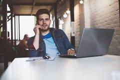 Νέα εργασία επιχειρηματιών στην αρχή, καθμένος στο γραφείο, εξετάζοντας την οθόνη φορητών προσωπικών υπολογιστών, χαμόγελο στοκ εικόνα με δικαίωμα ελεύθερης χρήσης