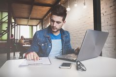 Νέα εργασία επιχειρηματιών στην αρχή, καθμένος στο γραφείο, εξετάζοντας την οθόνη φορητών προσωπικών υπολογιστών, χαμόγελο στοκ εικόνες