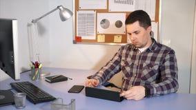 Νέα εργασία επιχειρηματιών στο γραφείο του που χρησιμοποιεί την ταμπλέτα του φιλμ μικρού μήκους