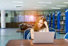 Νέα εργασία κοριτσιών σπουδαστών με το φορητό προσωπικό υπολογιστή σοβαρό στοκ φωτογραφία