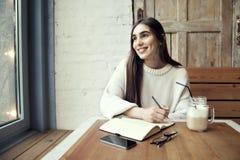 Νέα εργασία κοριτσιών hipster στον καφέ, με το σημειωματάριο σε έναν καφέ κοντά στο χρόνο μεσημεριανού γεύματος παραθύρων με τον  Στοκ Εικόνες