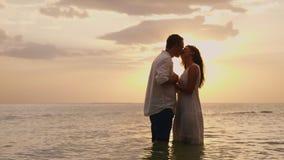 Νέα ερωτευμένη στάση ζευγών στη θάλασσα στο ηλιοβασίλεμα Εξέταση η μια την άλλη απόθεμα βίντεο