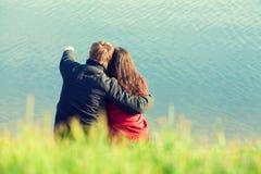 Νέα ερωτευμένη συνεδρίαση ζευγών στην ακτή στοκ φωτογραφία με δικαίωμα ελεύθερης χρήσης