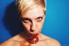 Νέα λευκή γυναίκα στο γλείψιμο χαμόγελου διασκέδασης κομμάτων lollipop Στοκ Εικόνες