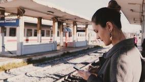 Νέα ευρωπαϊκά μηνύματα δακτυλογράφησης επιχειρηματιών στο smartphone σταθμό, που τονίζονται στο σιδηροδρομικό και πρόσφατο, τραίν φιλμ μικρού μήκους