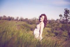 Νέα ευτυχής έγκυος γυναίκα που χαλαρώνει και που απολαμβάνει τη ζωή στη φύση Στοκ Εικόνες