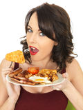 Νέα ευτυχής έκπληκτη γυναίκα που τρώει ένα πλήρες αγγλικό πρόγευμα Στοκ Εικόνες