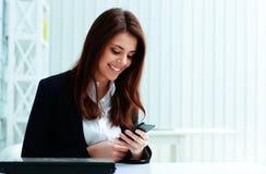 Νέα ευτυχής δακτυλογράφηση επιχειρηματιών στο smartphone της στοκ εικόνες