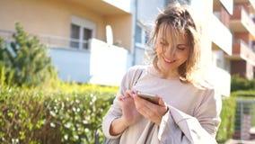 Νέα ευτυχής γυναίκα άνοιξη σε μια οδό πόλεων που εξετάζει το smartphone και το χαμόγελό της Φωτεινό ηλιόλουστο πρωί φιλμ μικρού μήκους