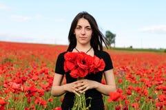 Νέα ευτυχής γυναίκα με μια ανθοδέσμη των κόκκινων παπαρουνών στοκ εικόνες