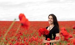 Νέα ευτυχής γυναίκα με μια ανθοδέσμη των κόκκινων παπαρουνών στοκ εικόνες με δικαίωμα ελεύθερης χρήσης