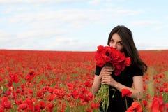 Νέα ευτυχής γυναίκα με μια ανθοδέσμη των κόκκινων παπαρουνών Στοκ Εικόνα