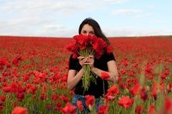 Νέα ευτυχής γυναίκα με μια ανθοδέσμη των κόκκινων παπαρουνών Στοκ Φωτογραφίες