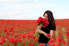 Νέα ευτυχής γυναίκα με μια ανθοδέσμη των κόκκινων παπαρουνών Στοκ εικόνα με δικαίωμα ελεύθερης χρήσης