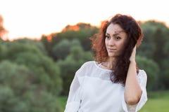 Νέα ευτυχής γυναίκα με τη μαύρη τρίχα υπαίθρια Στοκ εικόνα με δικαίωμα ελεύθερης χρήσης
