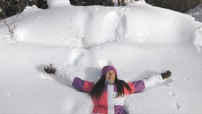 Νέα ευτυχής γυναίκα που κάνει τον άγγελο χιονιού φιλμ μικρού μήκους