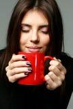 Νέα ευτυχής γυναίκα που μυρίζει το άρωμα του καφέ στοκ εικόνες