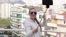 Νέα ευτυχής γυναίκα που παίρνει την αυτοπροσωπογραφία που στέκεται στη στέγη του σπιτιού που χρησιμοποιεί τηλεφωνική κάμερα κυττά φιλμ μικρού μήκους