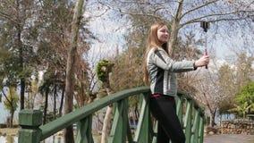 Νέα ευτυχής γυναίκα που παίρνει την αυτοπροσωπογραφία που στέκεται στην ξύλινη γέφυρα που χρησιμοποιεί τηλεφωνική κάμερα κυττάρων απόθεμα βίντεο