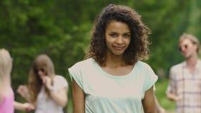 Νέα ευτυχής γυναίκα που χαμογελά και που εξετάζει τη κάμερα, που χορεύει στο φεστιβάλ μουσικής απόθεμα βίντεο