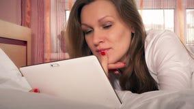 Νέα ευτυχής γυναίκα που χρησιμοποιεί τον υπολογιστή ταμπλετών που βρίσκεται στο άσπρο κρεβάτι απόθεμα βίντεο