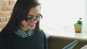 Νέα ευτυχής γυναίκα που χρησιμοποιεί τον υπολογιστή ταμπλετών σε έναν καφέ απόθεμα βίντεο