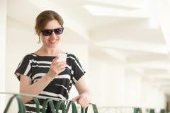 Νέα ευτυχής γυναίκα που χρησιμοποιεί app κινητό στο τηλέφωνο Στοκ Φωτογραφία