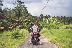 Νέα ευτυχής γυναίκα σε μια μοτοσικλέτα στο τροπικό δάσος ζουγκλών ενός τροπικού νησιού του Μπαλί, Ινδονησία μαύρη ελευθερία έννοι στοκ εικόνα με δικαίωμα ελεύθερης χρήσης