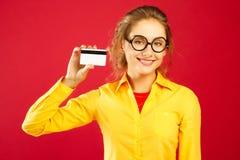 Νέα ευτυχής γυναίκα στα γυαλιά που κρατά την κενή πιστωτική κάρτα πέρα από το κόκκινο στοκ εικόνα με δικαίωμα ελεύθερης χρήσης