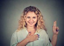 Νέα ευτυχής γυναίκα στα γυαλιά που κάνει μια υπόσχεση στοκ εικόνες