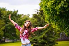 Νέα ευτυχής γυναίκα στο πάρκο στοκ φωτογραφίες