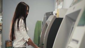 Νέα ευτυχής γυναίκα brunette που αποσύρει τα χρήματα από την πιστωτική κάρτα στο ATM στη λεωφόρο αγορών, φιλμ μικρού μήκους