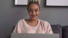 Νέα ευτυχής γυναίκα freelancer που χρησιμοποιεί το φορητό προσωπικό υπολογιστή στον καναπέ στο σπίτι απόθεμα βίντεο
