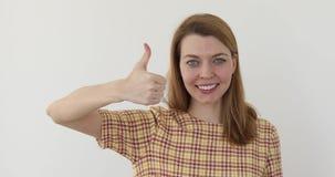 Νέα ευτυχής εύθυμη γυναίκα που παρουσιάζει αντίχειρα φιλμ μικρού μήκους