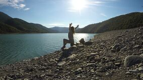Νέα ευτυχής θηλυκή συνεδρίαση στο riverbank στις ηλιαχτίδες και το τέντωμα, ελευθερία απόθεμα βίντεο