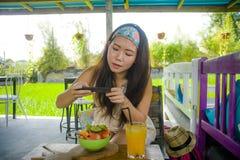 Νέα ευτυχής και αρκετά ψηφιακή ασιατική κινεζική γυναίκα νομάδων που παίρνει την εικόνα της σαλάτας φρούτων με την κινητή τηλεφων Στοκ Εικόνες