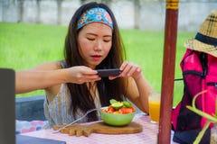 Νέα ευτυχής και αρκετά ψηφιακή ασιατική κινεζική γυναίκα νομάδων που παίρνει την εικόνα της σαλάτας φρούτων με την κινητή τηλεφων Στοκ εικόνες με δικαίωμα ελεύθερης χρήσης