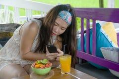 Νέα ευτυχής και αρκετά ψηφιακή ασιατική κινεζική γυναίκα νομάδων που παίρνει την εικόνα της σαλάτας φρούτων με την κινητή τηλεφων Στοκ φωτογραφία με δικαίωμα ελεύθερης χρήσης